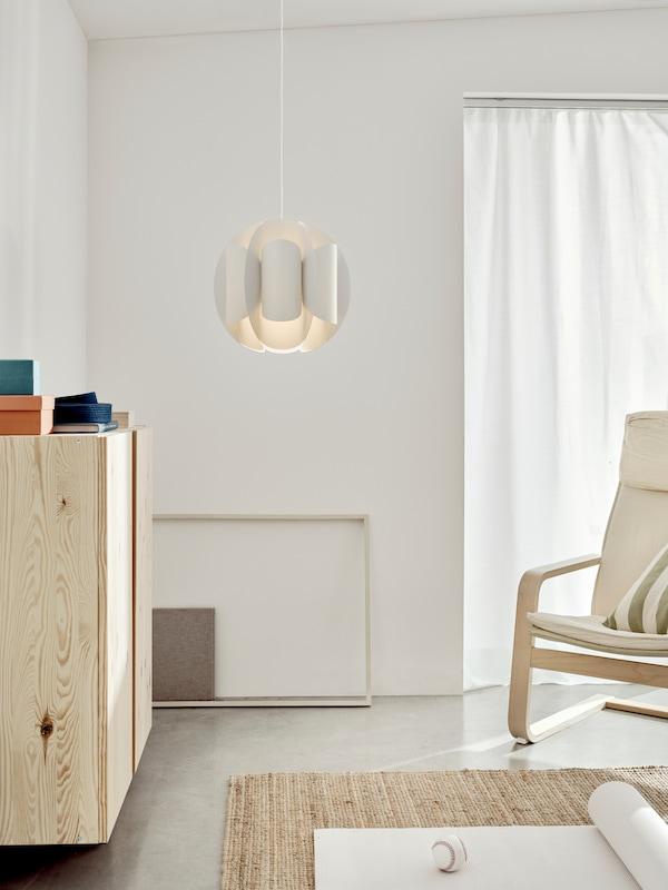 De TRUBBNATE hanglamp hangt midden in een lichte woonkamer.