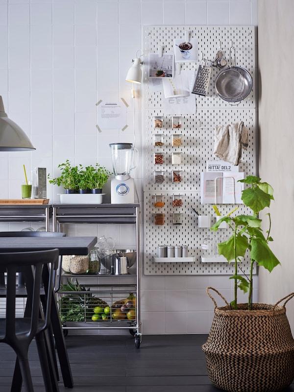 To SKÅDIS opslagstavler hænger på væggen i et køkken og organiserer krydderrier, køkkenredskaber og opskrifter.