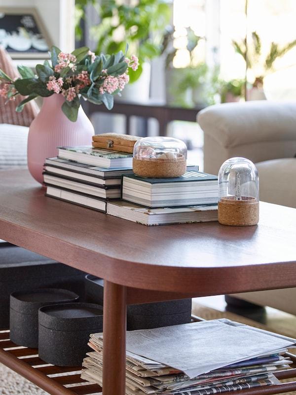 Masă de cafea LISTERBY IKEA maro dreptunghiulară pe care sunt păstrate cărți și cutii așezate pe o poliță înclinată dedesubt.