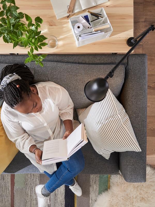 En kvinna läser en bok på en VIMLE bäddsoffa under en SKURUP arbets-/vägglampa som sitter fast i ett KULLABERG skrivbord bakom henne.