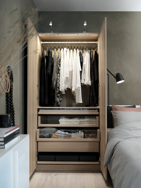 A white stained oak effect wardrobe with overhead lights is filled with hanging and folded clothes and stands next to a bed.