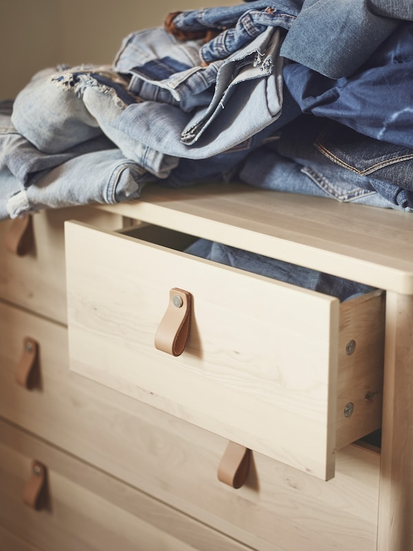 A pile of pairs of denim jeans lies on top of a birch BJÖRKSNÄS chest of drawers. The top drawer is slightly open.