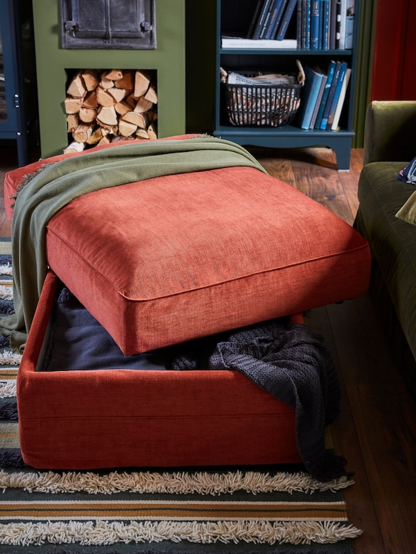 A light red footstool where the seat is open, throws are stored inside, with a dark blue-green bookcase behind.