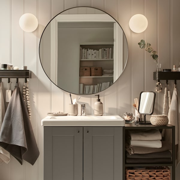 An ENHET washbasin with cabinet and open shelving unit against a white panelled wall with a round mirror above it.