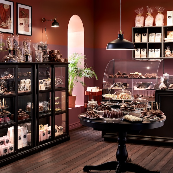 A confectionary shop, with display cabinets full of confectionaries, a table of the same, hanging lighting.
