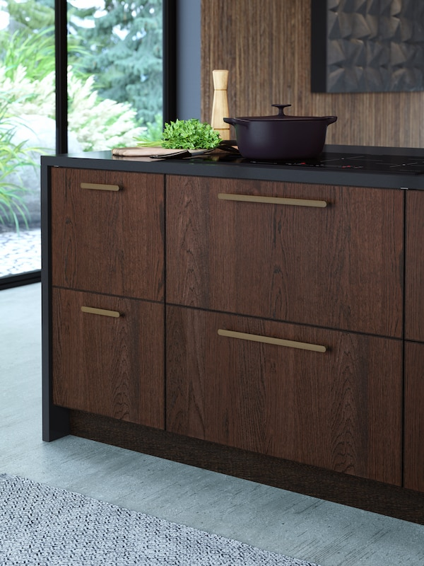 A kitchen island with wooden drawers and bronze handles, a chopping board with greens on it, and a black cooking pot.