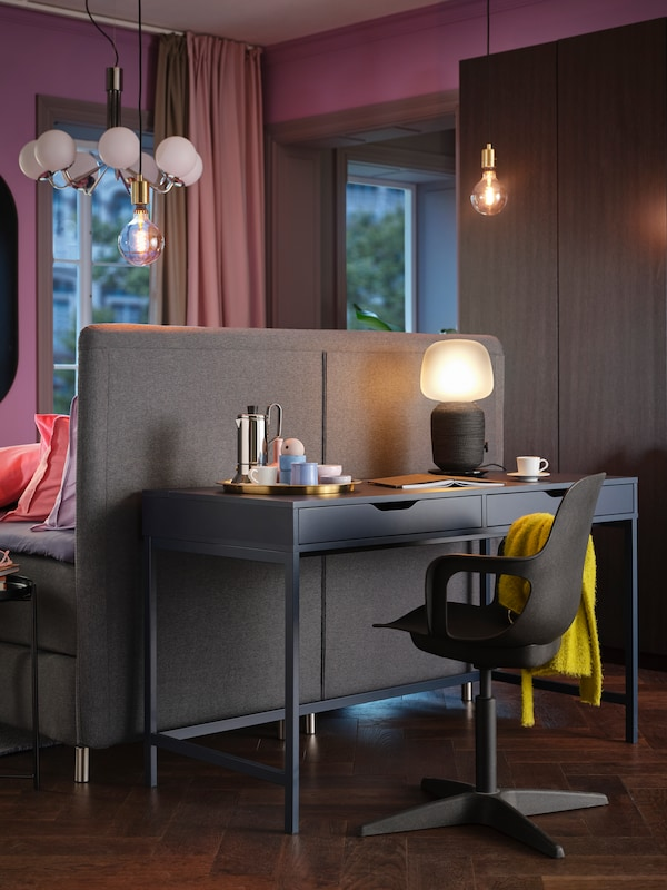 Part of a bedroom where an ALEX desk with a lamp and an ODGER swivel chair stand behind the headboard of a FINNSNES bed.