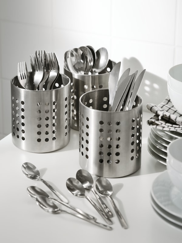 Six teaspoons on a table in front of three cutlery holders holding forks, knives, spoons, all from the FÖRNUFT cutlery set.