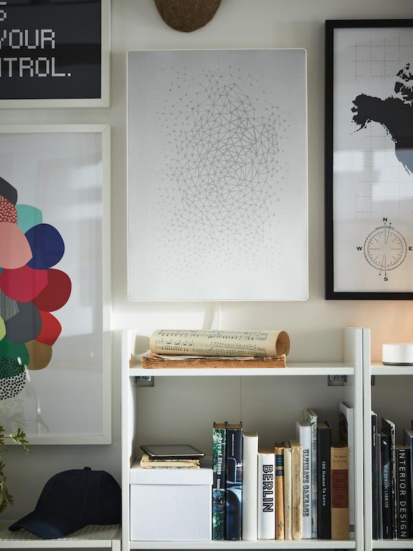 Indrammet kunst og en hvid billedramme med wi-fi-højttaler på væggen, hvide reoler, bøger, en kasket og noder.