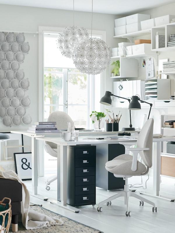 En lys kontorplass med to hvite SKARSTA sitte-/ståbord plassert overfor hverandre, to mørkegrå arbeidslamper og to kontorstoler.