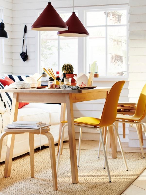 Cadires LEIFARNE de color groc i un tamboret de bedoll al costat d'una taula NORRÅKER i dos llums de sostre vermells, a prop d'un sofà blanc amb coixins.
