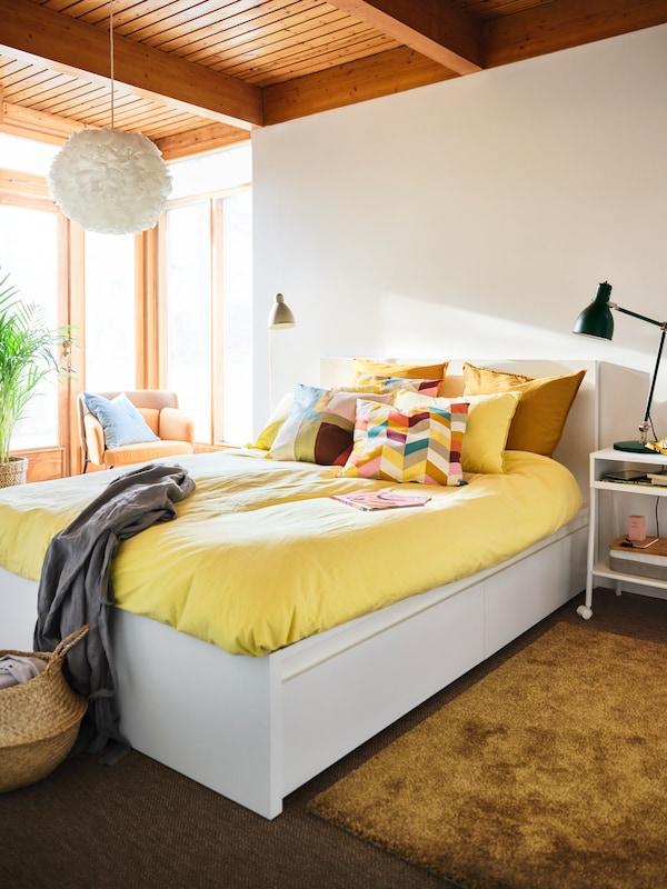 Sonniges, helles Schlafzimmer mit einem weißen MALM Bettgestell mit gelber Bettwäsche. In der Mitte liegt ein Kissen mit einem HANNELISE Kissenbezug.