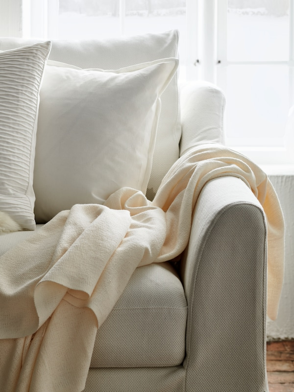 A section of a white sofa with white cushions and beige blankets, by a large window in a bright room.