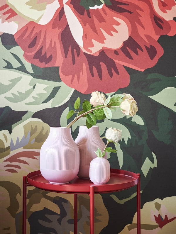 GRADVIS vases on a red side table in front of the bold floral wallpaper in the background.