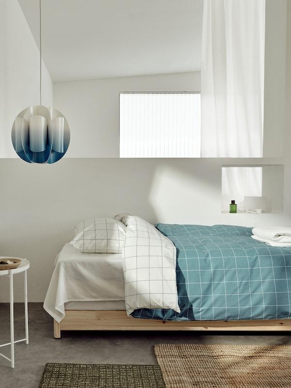 Cama hecha con la funda nórdica VITKLÖVER, a juego con la pantalla para lámpara de techo TRUBBNATE en azul y blanco.
