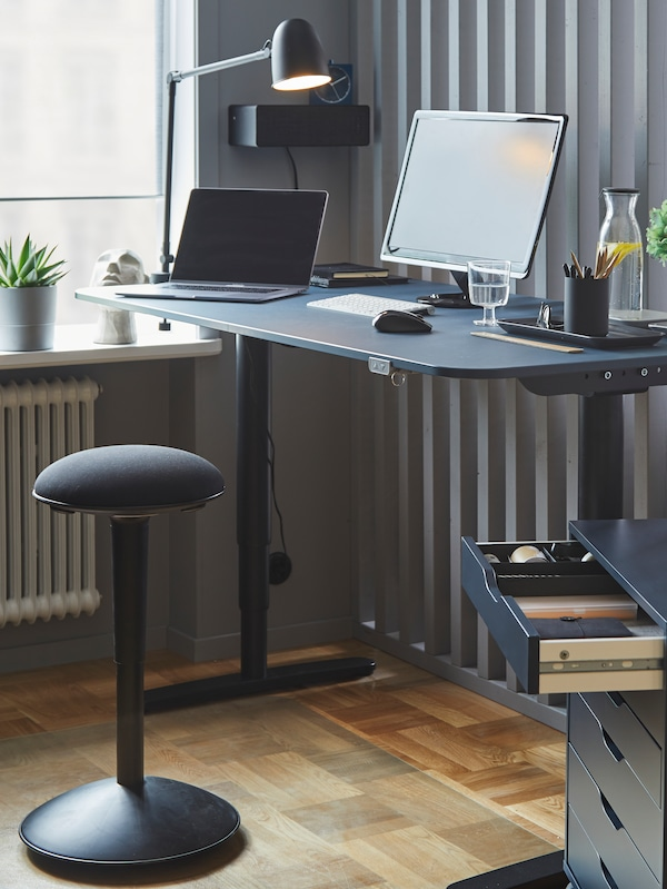 A black NILSERIK active sit/stand support with a black BEKANT standing desk.