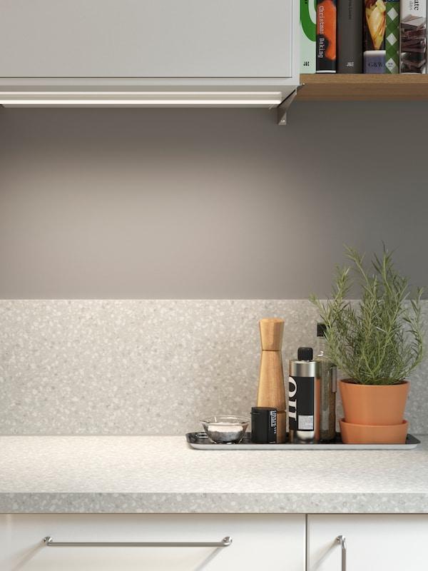 Prikaz kuhinje s usklađenim laminatnim zidnim pločama i laminatnom kuhinjskom radnom pločom s efektom minerala.