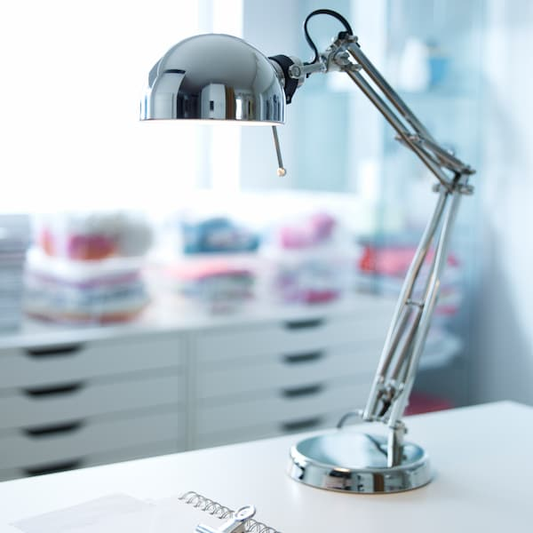 A nickel-plated FORSÅ work lamp sits on a white surface near some ALEX drawer units on castors which are under a window.