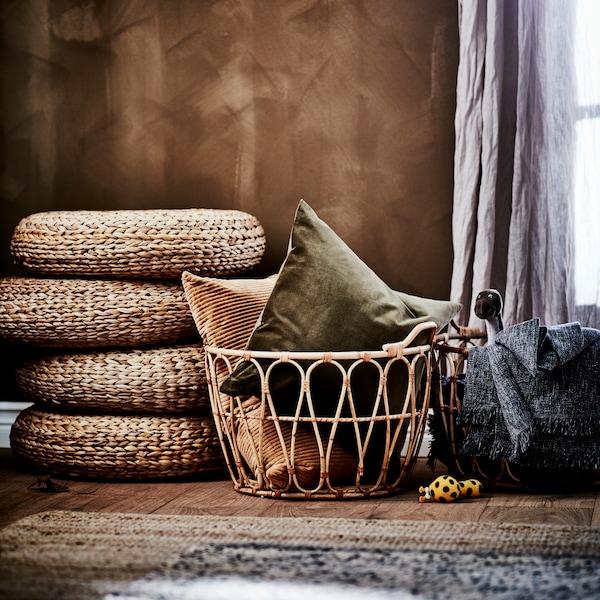 Tabourets tressés empilés les uns sur les autres, avec un panier contenant des coussins devant une fenêtre habillée de rideaux.