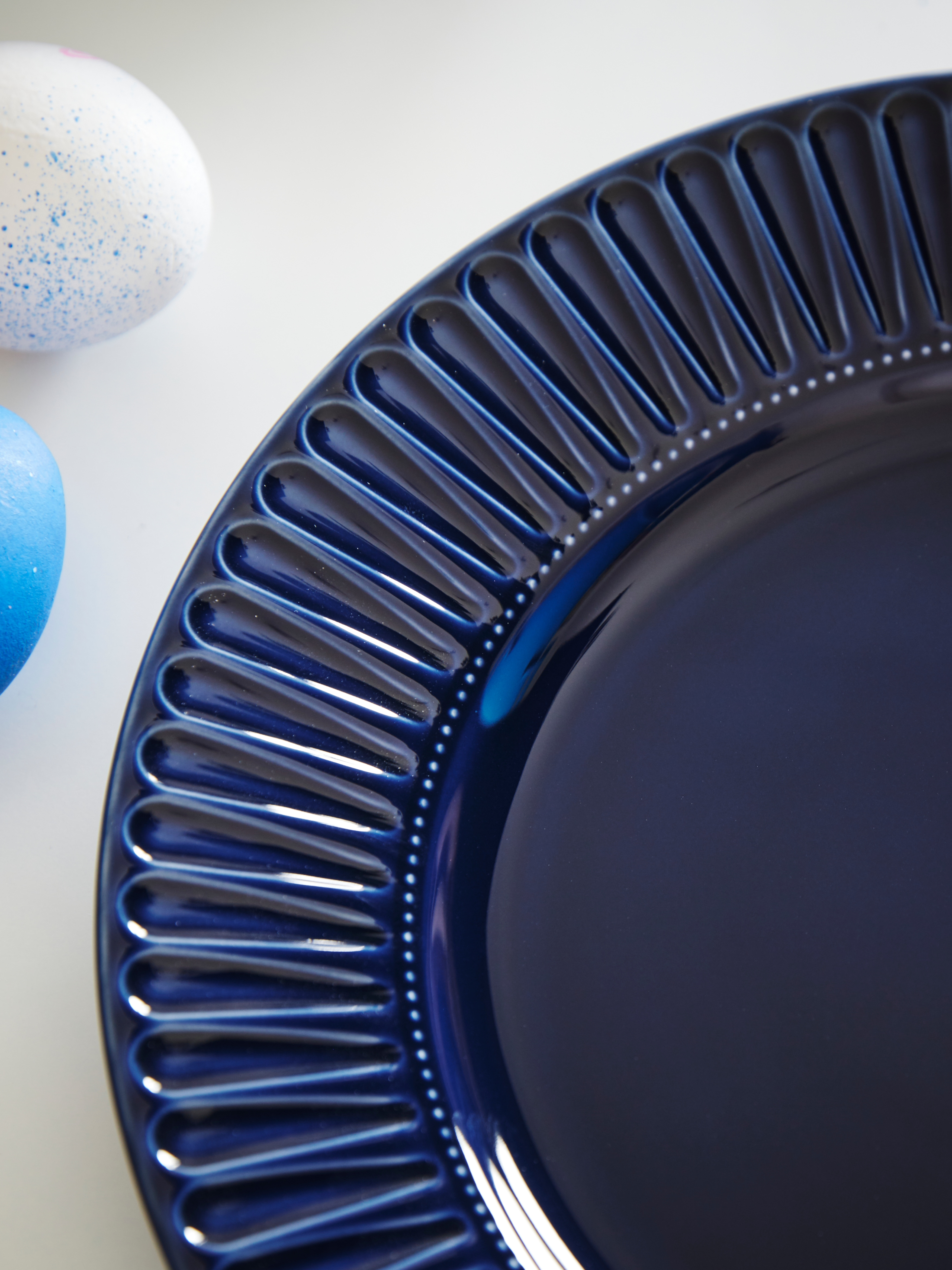 Krupni plan fasetiranog tamnoplavog porculanskog STRIMMIG tanjura pokraj dva pjegava plava jaja.