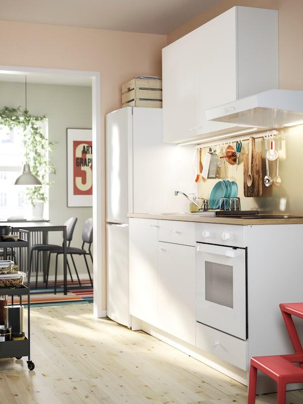 Bílá kuchyň KNOXHULT se spodními skříňkami a nástěnnou skříňkou, lednicí a jídelním koutem v pozadí.