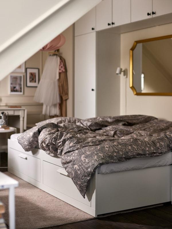 Egy kinyitott BRIMNES kanapéágy bézs/sötétszürke ágyneművel, mögötte fehér gardróbokkal, fölötte egy aranyszínű keretes tükörrel.