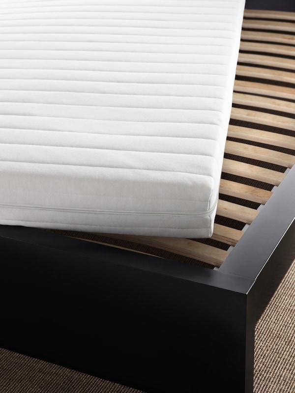 سرير بهيكل أسود-بني ومرتبة بيضاء بزاوية من أعلى لتكشفعن قاعدة سرير شرائحية LURÖY.