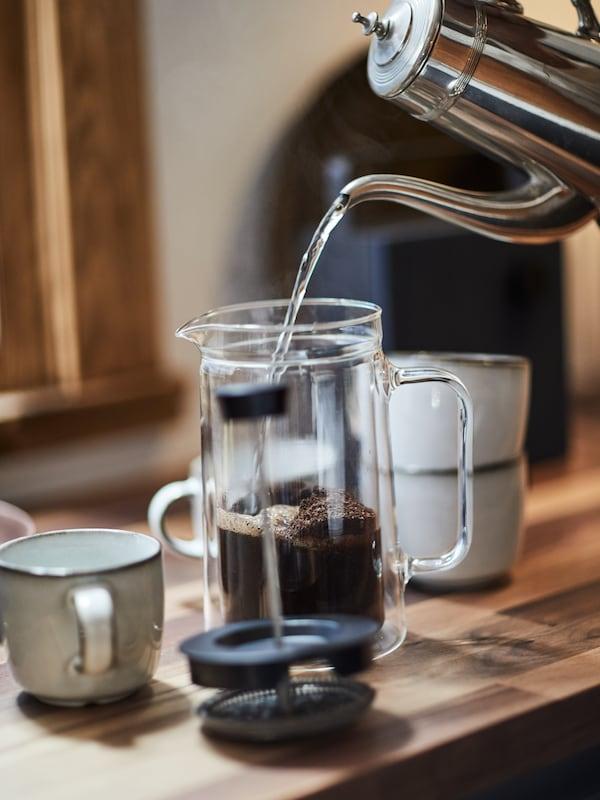 ماء يتم صبه من إبريق فضي في ماكينة صنع قهوة EGENTLIG موضوعة على سطح عمل خشبي.