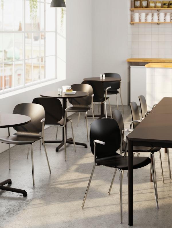 Un gruppo di tavoli scuri con sedie coordinate vicino a diversi piccoli tavoli rotondi con sedie accanto a una fila di finestre - IKEA