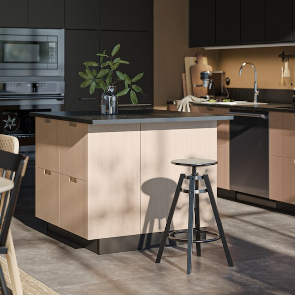 The sun is falling on a black DALFRED bar stool, next to a kitchen island with FRÖJERED kitchen fronts in light bamboo.