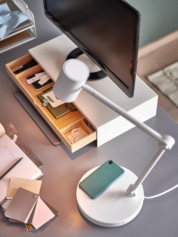 مصباح عمل NYMÅNEأبيض مع شاحن هاتف في قاعدته، وشاشة كمبيوتر على حامل شاشة مع درج مفتوح.