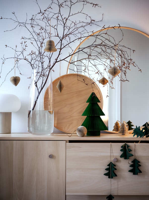 A green tree-shaped decoration is on an ERSNÄS sideboard beside a BERÄKNA vase with a branch and hanging decorations.