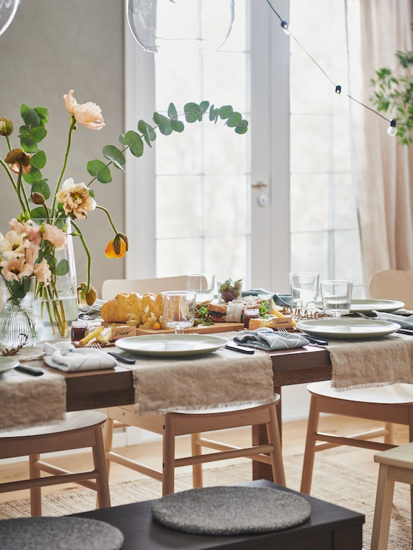 A MÖRBYLÅNGA table festively set with natural-colour AINA fabric, FÄRGKLAR plates, flowers in vases and various decorations.
