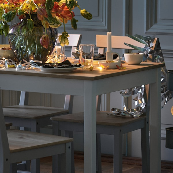 A LERHAMN table, set with tableware and flowers in a vase, stands in a room along with some GAMLEBY chairs.