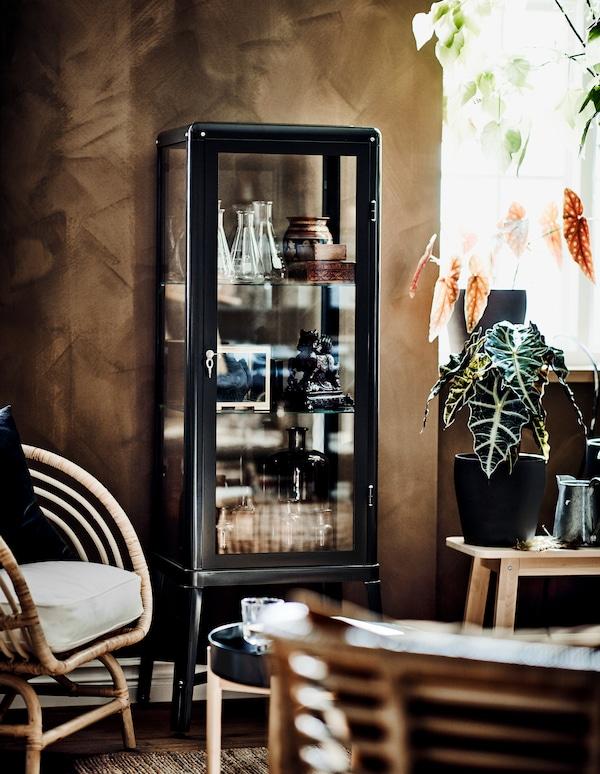 Une vitrine est remplie de diverses décorations et objets de collection. Au premier plan, il y a de confortables chaises en osier.