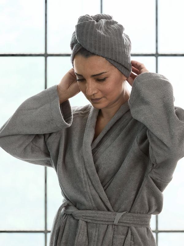Devant la fenêtre de sa salle de bain, une femme vêtue d'un peignoir ROCKÅN gris ajustant une serviette pour cheveux TRÄTTEN gris foncé sur sa tête.