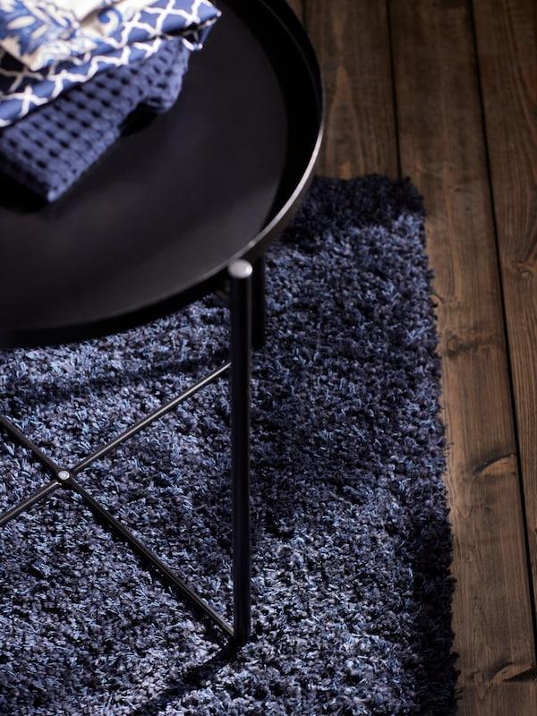 Kék színű, mintás hálószobai textíliák egy fekete GLADOM tálcaasztalon, ami egy sötétkék szőnyegen áll.