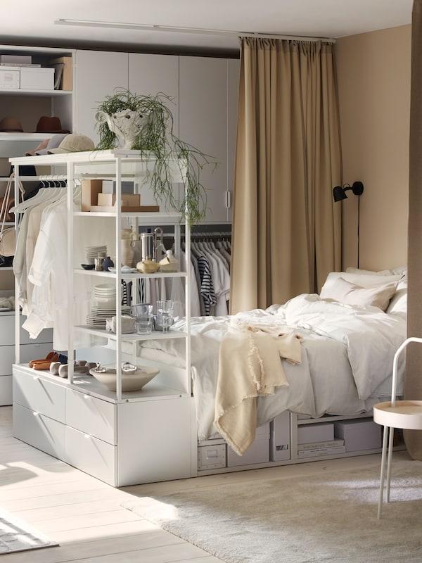 Fehér PLATSA ágykeret négy fiókkal, fehér ágyneművel az ágyon, a ruhákkal a kereten, tárgyakkal a polcokon.