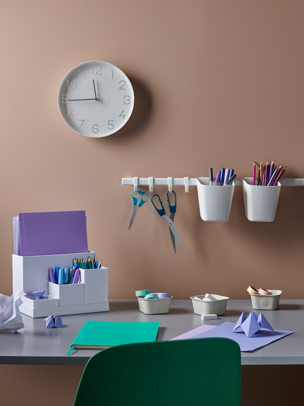 Several desk organizers on a desk with a rail and a clock mounted on a peach wall in the background.
