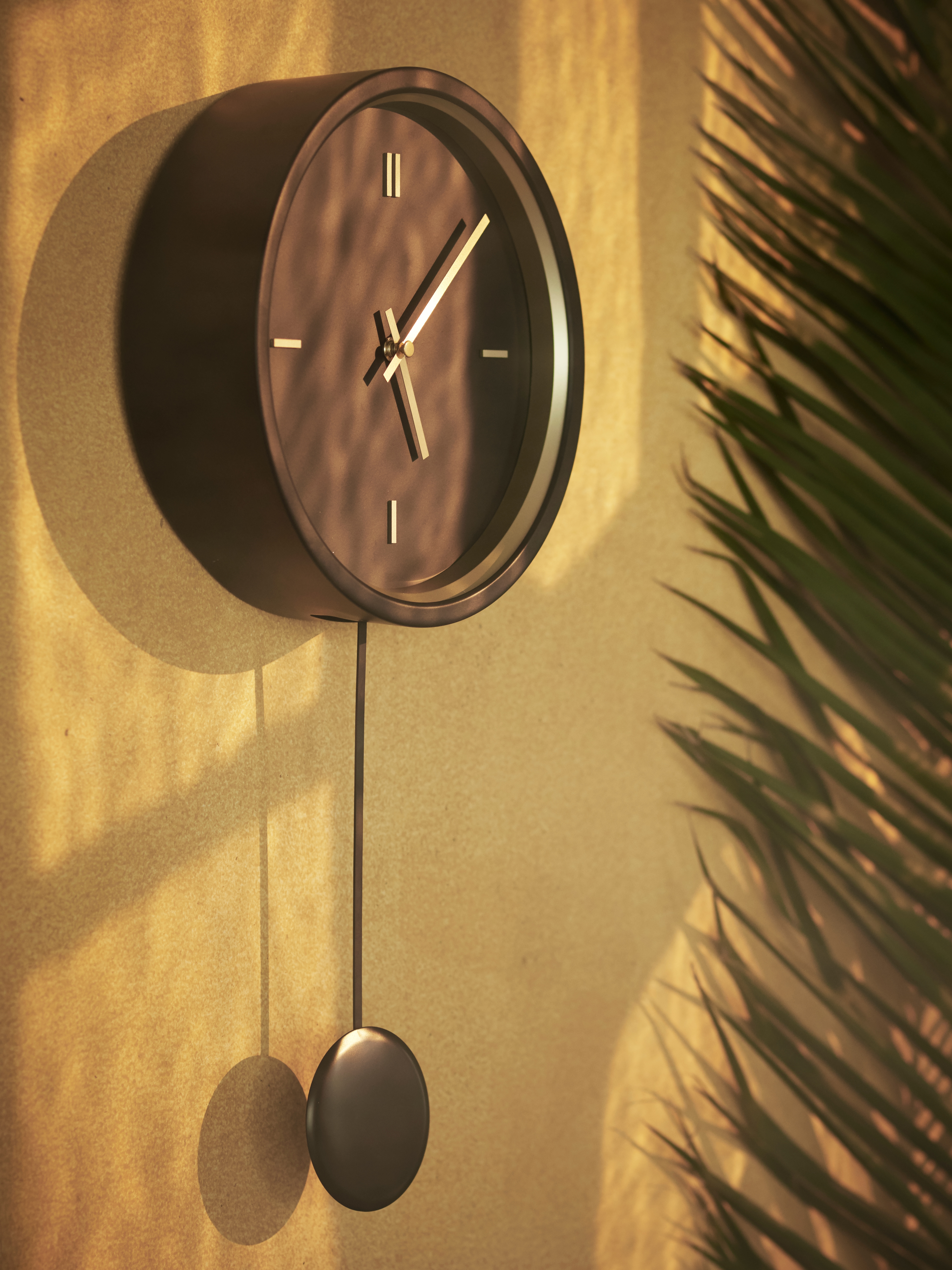A round-faced, minimalistic black STURSK wall clock with a pendulum and gold details is on a yellow, shaded wall by a plant.