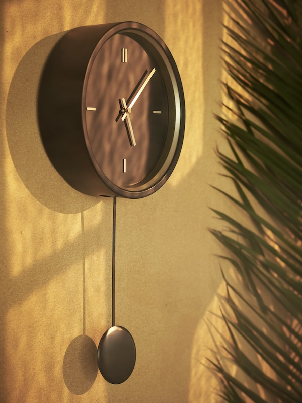 A close-up of the black STURSK wall clock with gold details and hands, hung up on a golden-brown wall.