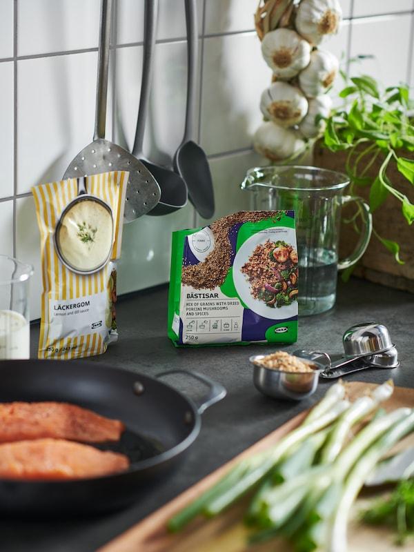 Paquetes de mix de cereales BÄSTISAR con setas y salsa de limón y eneldo LÄCKERGOM rodeados de accesorios de cocina.