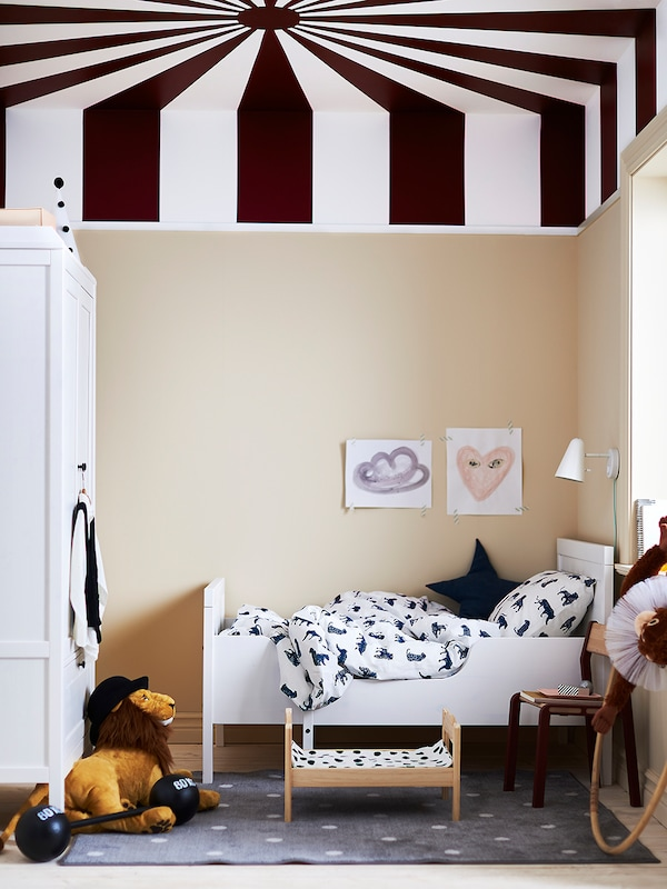 A child's room with a bed with URSKOG bed linen. There's a lamp on the wall and a DJUNGELSKOG soft toy lion on the floor.