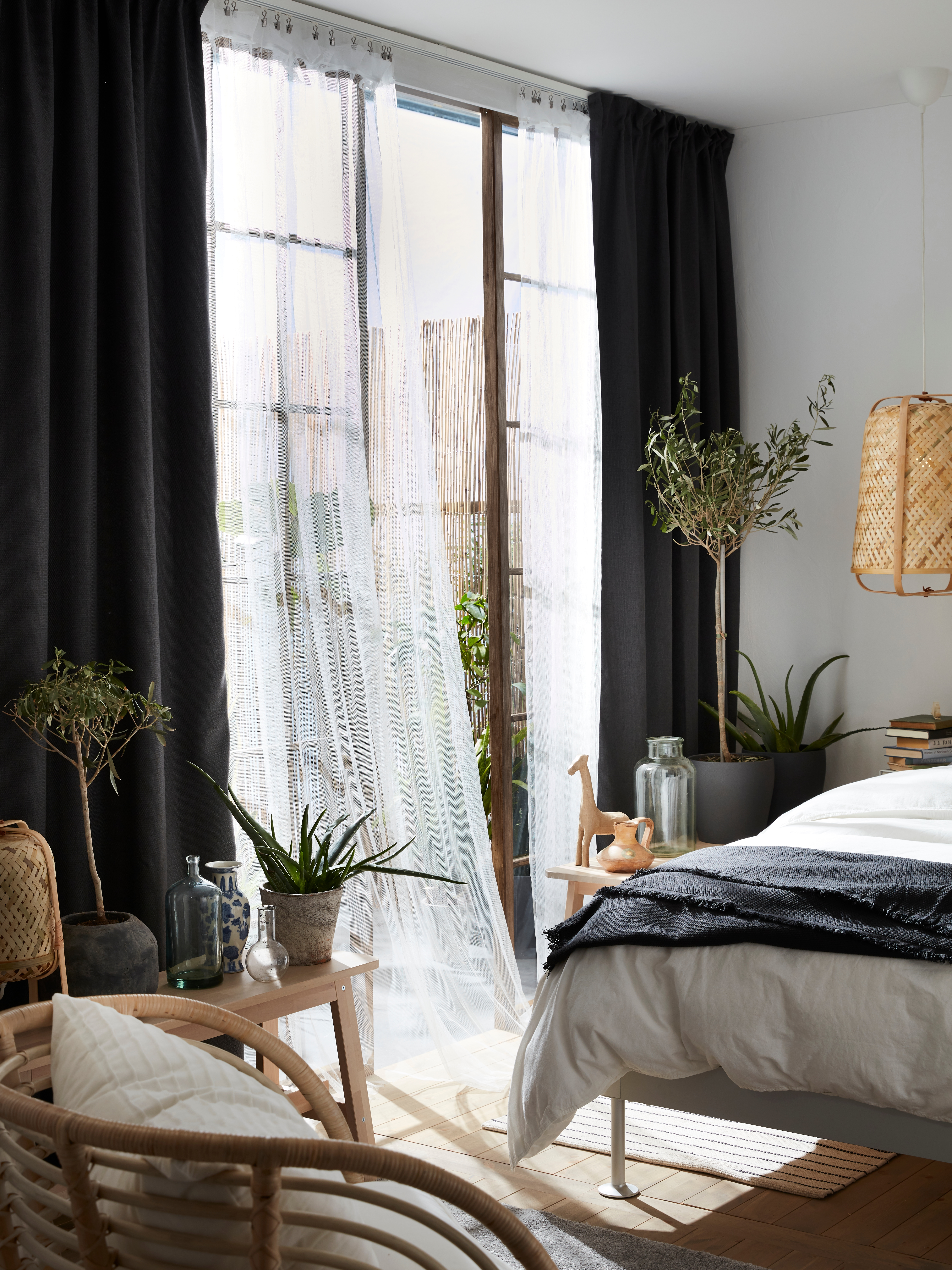 A light-filled bedroom with large glass doors behind flowy, white LILL net curtains layered under thick darkening curtains.