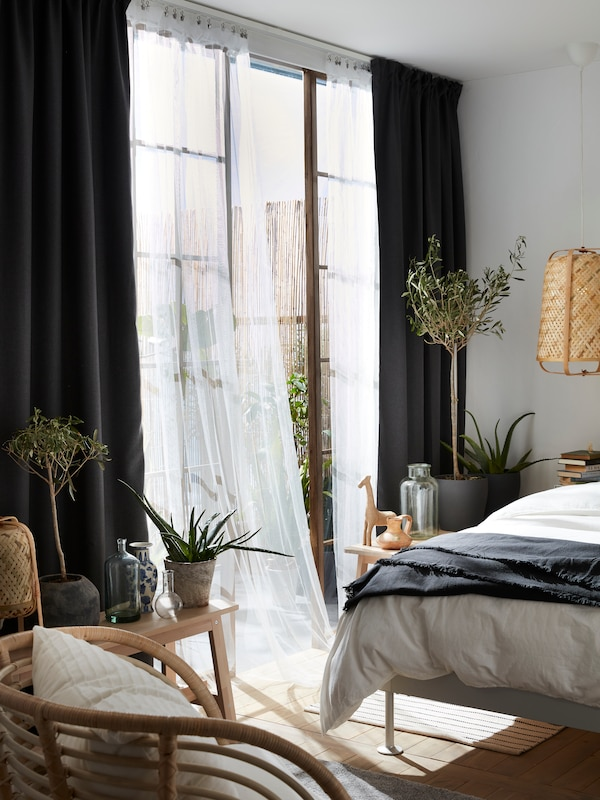 Une journée ensoleillée, un rideau LILL, blanc et léger, qui bouge au gré du vent de la fenêtre entrebâillée dans une chambre à coucher.