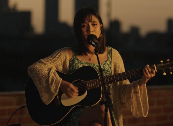 A cantautora NIKI cantando e tocando a guitarra.