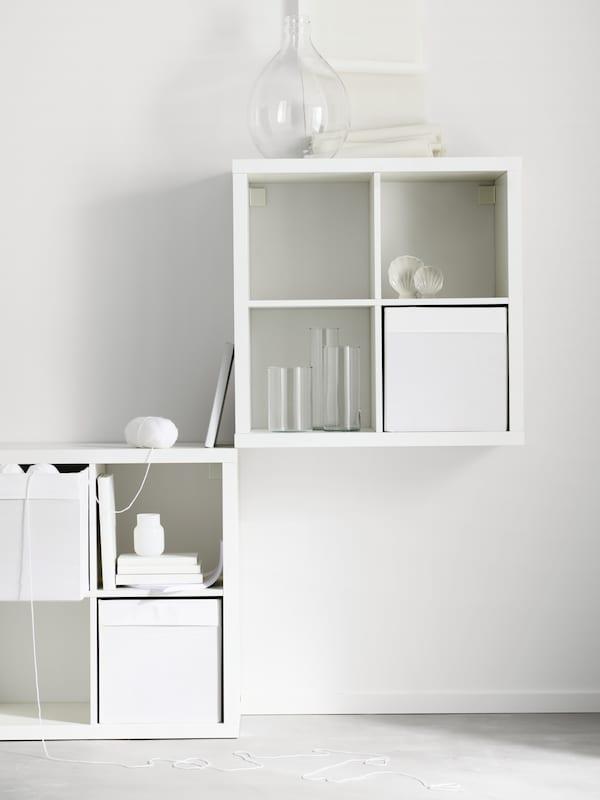 Dve beli KALLAX enoti s štirimi policami, postavljeni diagonalno na steni, na policah pa so knjige, steklene vaze in beli zaboji za shranjevanje.