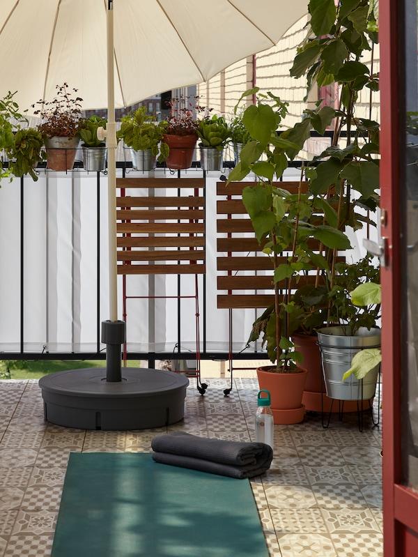 Una mesa y una silla plegadas y apartadas para dejar sitio a una esterilla de yoga, extendida en el suelo de un balcón.