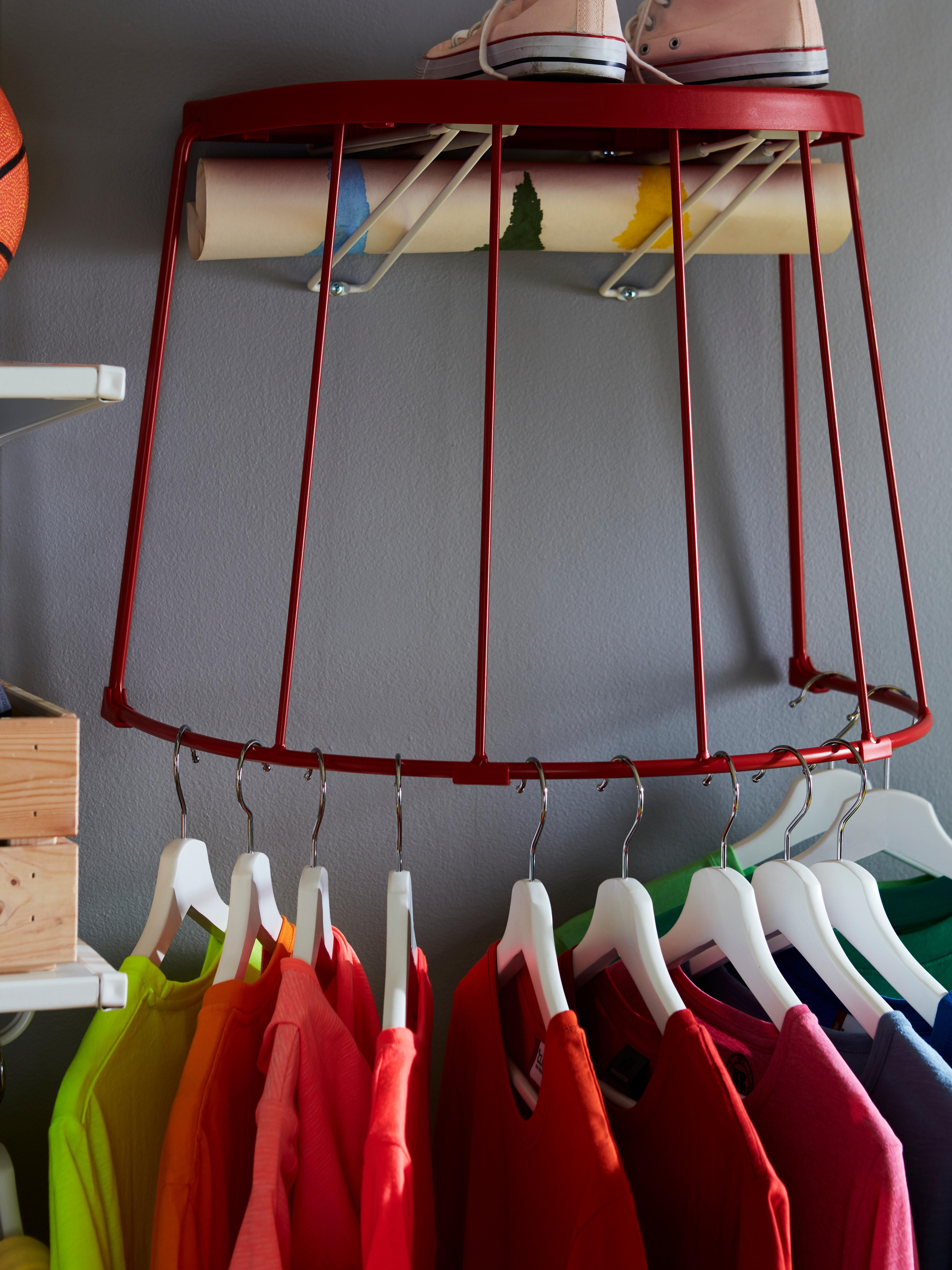 Ein roter TRANARÖ Hocker/Beistelltisch für innen und außen ist wie ein Regal an eine Wand montiert. An seinem halbkreisförmigen Fuß hängen Kleider.