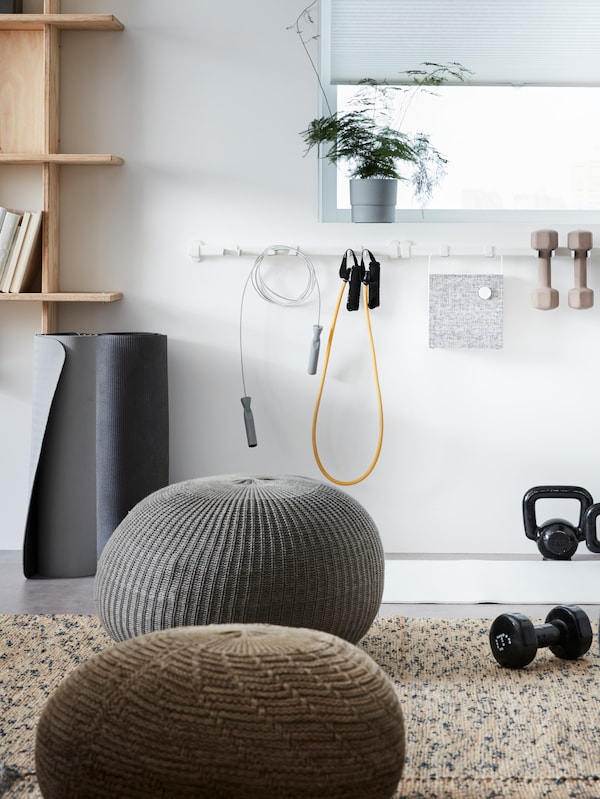 SANDARED pouffes scattered in a relaxation area of an office, with a VAJERT white rail hung with sport equipment.